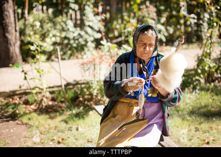 Senior woman spinning thread on spindle while sitting on bench at yard - Stock Image