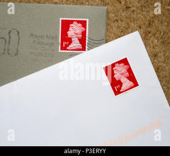 Looking down at letters in envelopes with red First class postage stamps, England, UK - Stock Image
