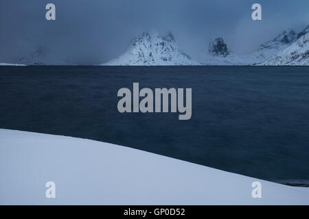 Mountain vanish into approaching winter storm, Reinefjord, Moskenesøy, Lofoten Islands, Norway - Stock Image