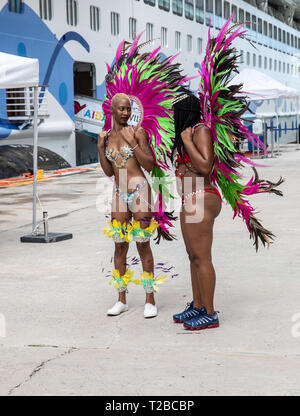 Two ladies dress up in local costume to welcome cruise ship passengers to Antigua, The Caribbean - Stock Image