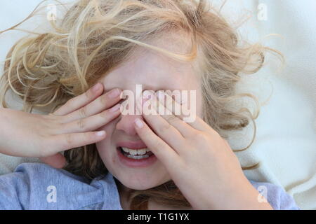 Portrait of a tired child in pain with her hands in front of her eyes - Stock Image