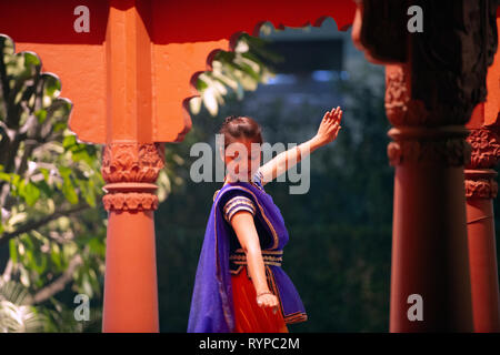 A young lady performs a traditional dance in a brightly colored costume in India. - Stock Image