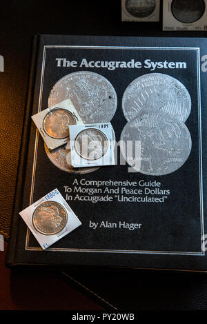 The Accugrade System Reference Book by Alan Hager considered by many the first one to offer a grading system for coins pictured with Morgan Dollars - Stock Image