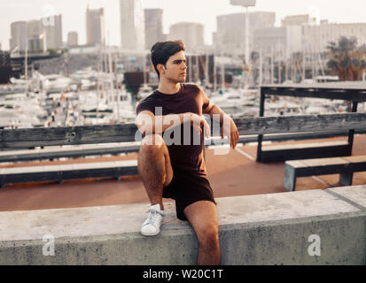 Young athletic man after running at park with skyscrapers background - Stock Image