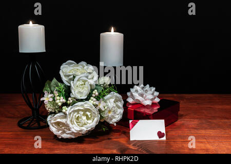Beautiful bouquet of arranged flowers white candles on a holder with a present and a card on a wooden table. mothers day, Easter, valentines, birthday - Stock Image