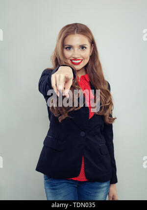 Pointing hand of happy woman on gray background - Stock Image