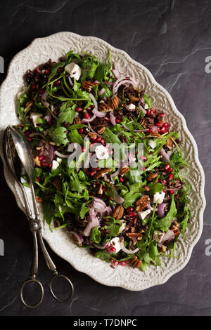 Rocket, pomegranate and black rice salad on an oval serving dish. - Stock Image