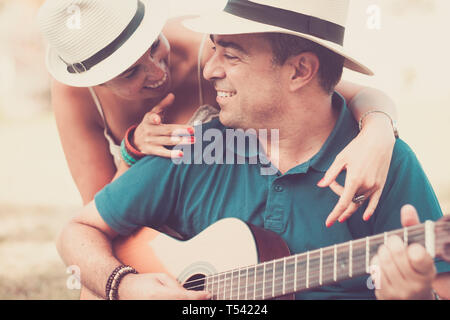 Romantic hug an colors with cheerful happy middle age people in love playing a guitar together looking and smiling - relationship for middle age adult - Stock Image