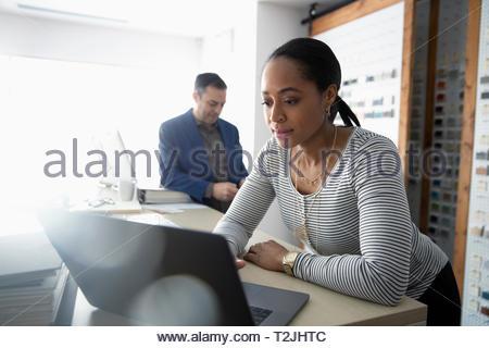 Female interior designer using laptop in design studio - Stock Image