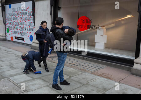 An Asian family struggle with a blue boot outside a window display that is part of a design theme called 'State of the Arts', at the Selfridges department store on Oxford Street, on 4th March 2019, in London England. State of the Arts is a gallery of works by nine crtically-acclaimed artists in Selfridges windows to celebrate the power of public art. Each of the artists are involved in creating a site-specific artwork at one of the new Elizabeth line stations as part of the Crossrail Art Programme. - Stock Image