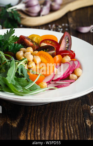 Healthy vegan bowl. Veggie chickpeas salad with fresh vegetables, colorful mix cherry tomatoes, arugula, radishes, cucumbers on wooden table, plant ba - Stock Image