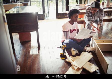 Women reading instructions, assembling furniture - Stock Image