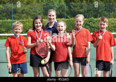 Portrait Of Winning School Tennis Team With Medals - Stock Image