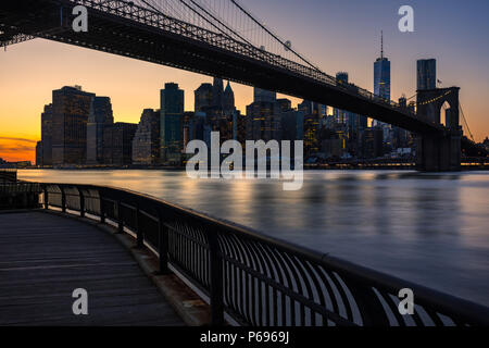 Lower Manhattan skyscrapers and the Brooklyn Bridge at sunset from Empire Fulton Ferry Park (Brooklyn). Manhattan, New York City - Stock Image