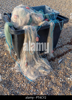 Nylon fishing nets spilling from a grey plastic container on a pebble beach - Stock Image