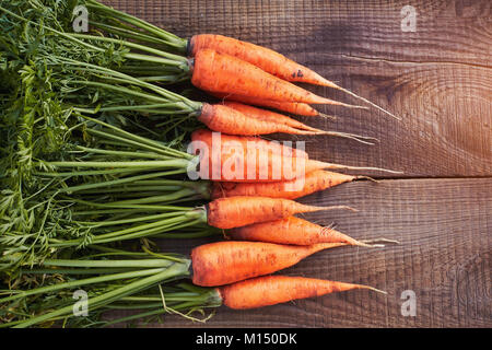 Carrots with leaves beam isolated on wood background. Fresh carrot with home garden farm. Close up - Stock Image