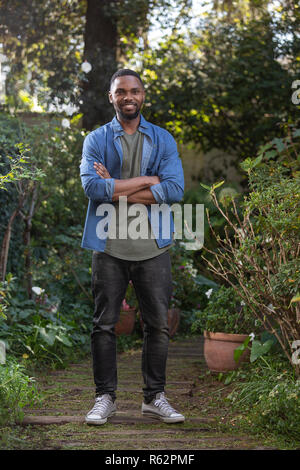 An African man standing in a garden with arms crossed - Stock Image