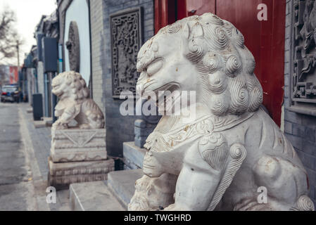 Lion statues in traditional hutong residential area in Dongcheng district of Beijing, China - Stock Image