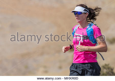 Female runner running on open road in arid landscape - Stock Image