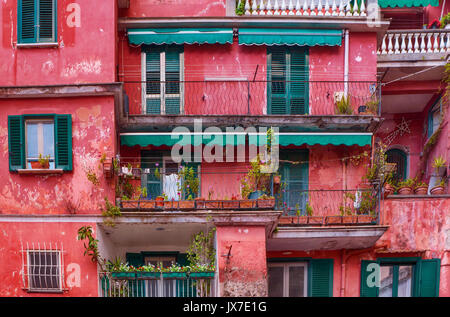 Street view of artistic vibrant pink and green building facade with shuttered windows, balconies, and potted plants. Italy's Amalfi Coast. - Stock Image