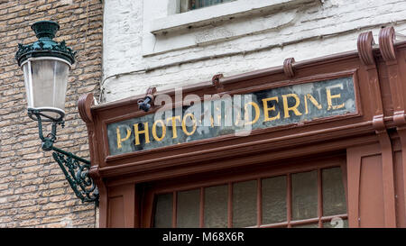 Photo Moderne signage adorns the photographic shopfront facade in the ancient city of Bruges - Stock Image