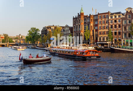 Tourist cruise boats on Amstel river in Amsterdam, Netherlands - Stock Image