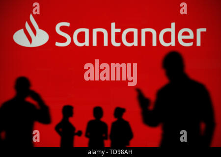 The Santander Bank logo is seen on an LED screen in the background while a silhouetted person uses a smartphone in the foreground (Editorial use only) - Stock Image