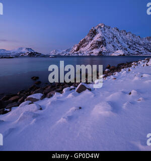 Sørfjellet mountain peak rising over winter coastline near Henningsvær, Austvågøy, Lofoten Islands, - Stock Image