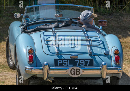 An elderly lady driver of a classic MGA, open top, British sports car, fully restored in pale blue paint, just about to drive off on a hot summer day. - Stock Image