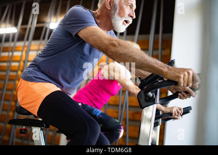 Mature fit couple exercising in gym to stay healthy - Stock Image