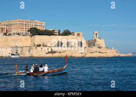 Tourists on a traditional Maltese dghajsa ferry boat in Malta Grand Harbour with the fortifications of Valletta - Stock Image