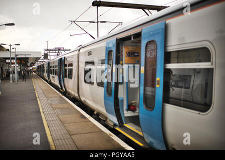 empty train waiting on the platform at Cambridge station on a cloudy afternoon - Stock Image