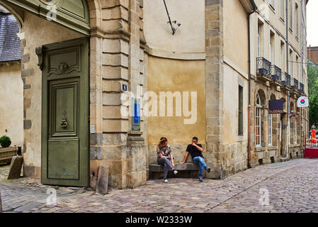 A couple of people sitting outside the Hotel de Ville in Rennes, the capital of Brittany, France - Stock Image
