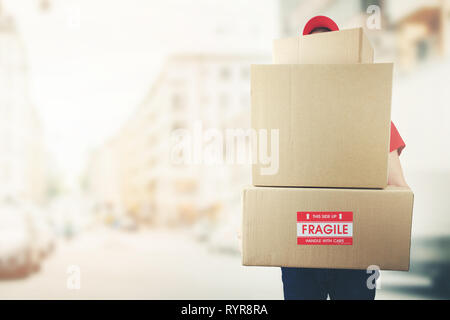 delivery man with stack of boxes standing on the street. copy space - Stock Image