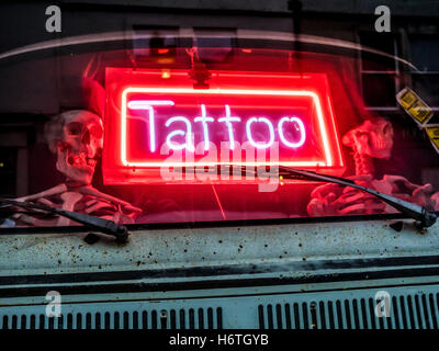 Two Skeletons driving a Volkswagen VAN in a Tattoo parlor - Stock Image