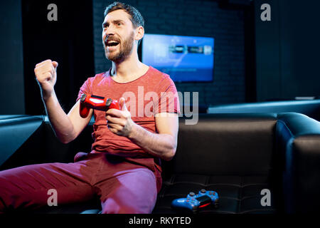 Happy man winning in video game playing with gaming console on the couch in the dark room of the playing club - Stock Image