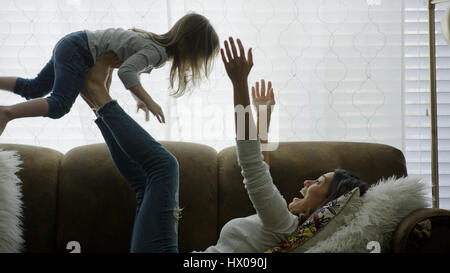 Profile of laughing playful mother lifting daughter in mid-air and playing on sofa - Stock Image