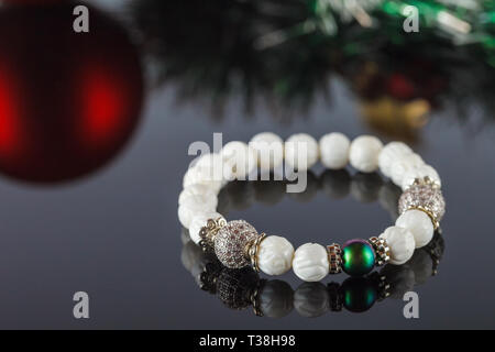 Exquisite women's bracelet made of natural stones, agate and sugar quartz with accessories that are encrusted with cubic zirconias. Close-up. Studio l - Stock Image