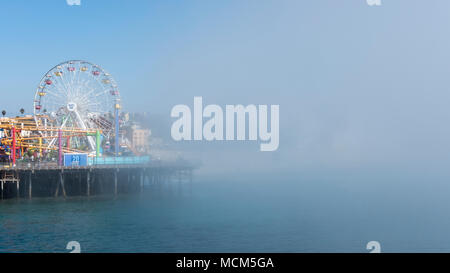 Sudden fog covering fast the Venice Beach towards the iconic ferris wheel from the famous Santa Monica Pier, Los Angeles, California, USA - Stock Image