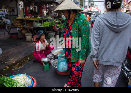 Elderly Asian woman in bright outfit with Chinese hat shopping for vegetables at a street market, Ho Chi Minh City, Vietnam. - Stock Image