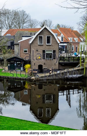The building of Rederij Alliantie BV, a specialist in ship repair, reflects in the moat that surrounds the old Hanseatic city of Elburg, Netherlands. - Stock Image