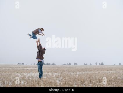 Parent throwing child in air - Stock Image