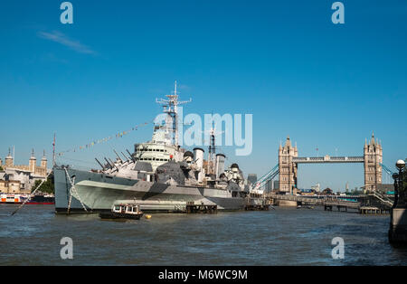 HMS Belfast moored on the river Thames, with London landmark Tower Bridge in the background, London, England, UK - Stock Image