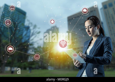 young woman using tablet PC and Internet of Things concept. smart city. wireless communication network. abstract - Stock Image