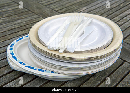 Assorted paper plates with plastic cutlery on garden table. - Stock Image