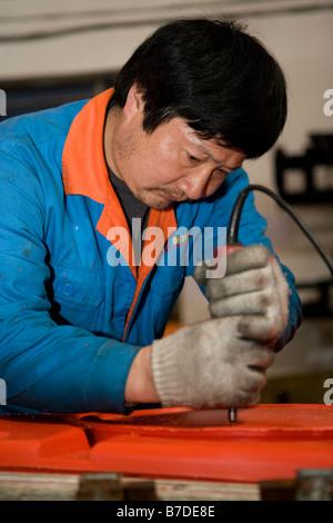 worker making kayaks shanghai china - Stock Image