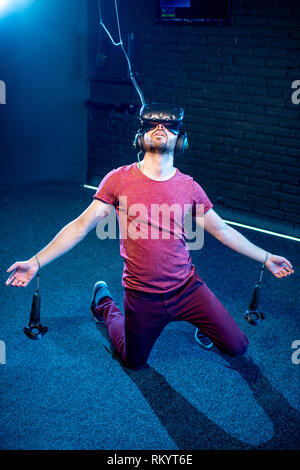 Wounded man falling down during the virtual reality shooting in the playing room - Stock Image
