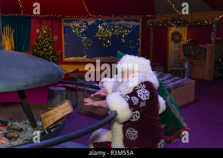 Eden Project, Cornwall, UK. 23rd November 2018. The Eden project's Christmas celebrations get underway this weekend, with light and shadow experience in the biomes, ice skating and a magical experience with Santa and his Elves. Santa warming his hands on the log fire inside the Xmas HQ Credit: Simon Maycock/Alamy Live News - Stock Image