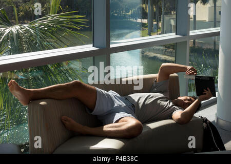 Student reads book while laying on sofa in sun at University of Miami, Florida, student union. - Stock Image