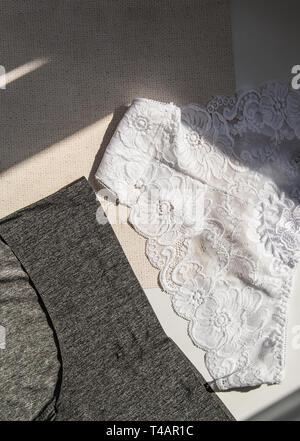 White lace sexy panties vs black textile bikinis, vertical shot, top view. - Stock Image